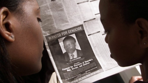 FILE PHOTO: READERS LOOK AT A PICTURE OF A RWANDAN WANTED FOR ALLEGED ROLE IN  RWANDA'S 1994 GENOCIDE.