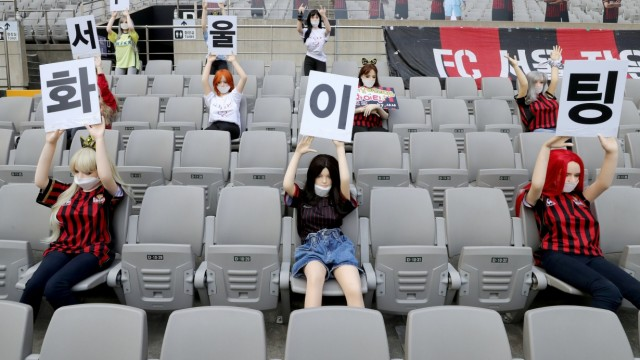 Mannequins are placed in spectator seats to cheer during football match in Seoul