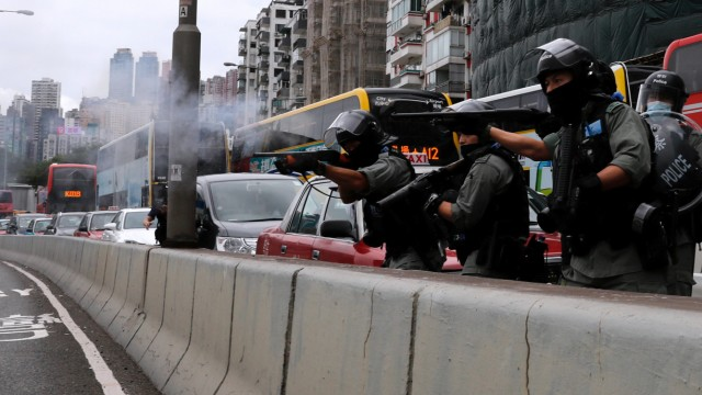 Riot police use rubber bullets to disperse anti-government protesters during a march against Beijing's plans to impose national security legislation in Hong Kong