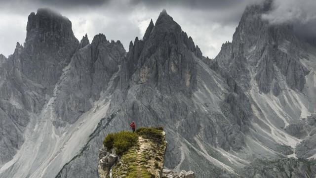 Bergsteiger mit roter Jacke steht auf einem Grat, hinten Berggipfel und spitze Felsen, dramatische Wolken, Cimon di Crod