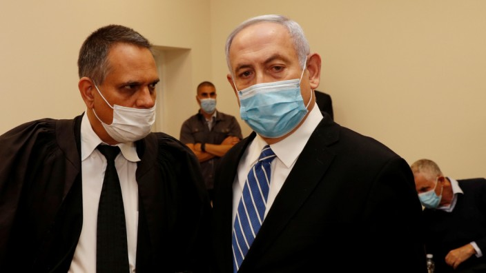 Israeli Prime Minister Benjamin Netanyahu, wearing a mask, stands inside the courtroom as his corruption trial opens at the Jerusalem District Court
