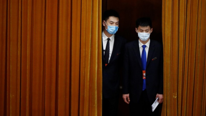 Security personnel keep watch before the second plenary session of NPC in Beijing