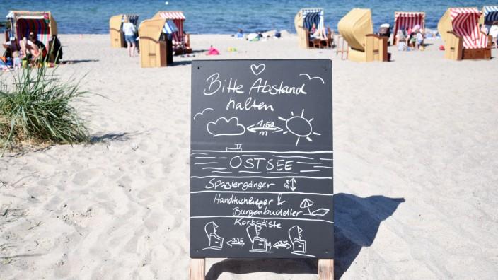 Die Gäste am Ostseestrand Niendorf werden auf einem Schild aufgefordert, Abstand zu halten.