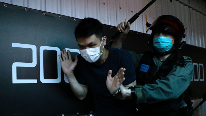 Anti-government protester detained by riot police in Hong Kong