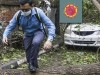 A man makes his way tpast a tree fallen in the middle of a road after Cyclone Amphan hit the region in Kolkata, India, Thursday, May 21, 2020