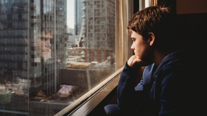 Tween boy looking out a window at tall buildings of the city outside. Toronto, ON, Canada ,model released, Symbolfoto PU