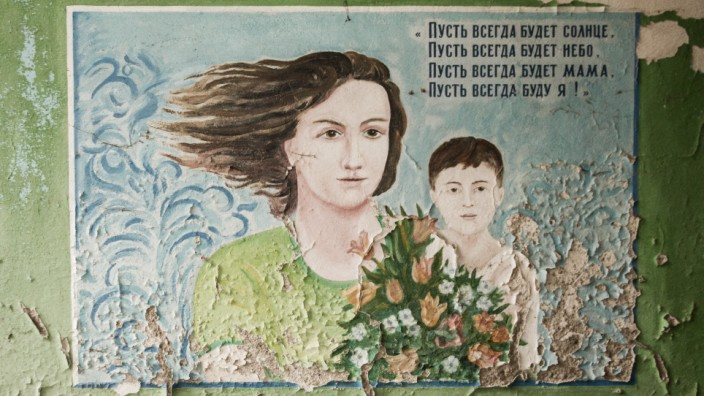 POST SOVIET LANDSCAPES, MOLDOVA. Poster from the soviet era painted on the wall of a ruined pediatric centre depicting a