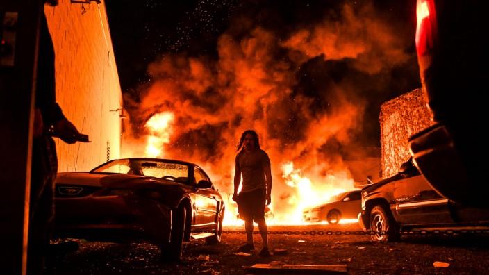 Proteste in den USA: Ein Mann versucht sich von brennenden Autos zu entfernen. Das Bild wurde am 29. Mai 2020 in Minneapolis während der Proteste aufgenommen.