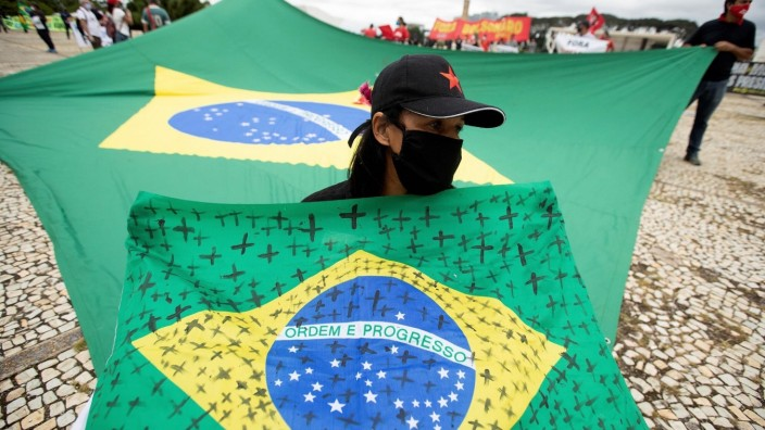 A woman holds a Brazilian flag with black crosses painted on to remember victims of covid-19, while participating in a