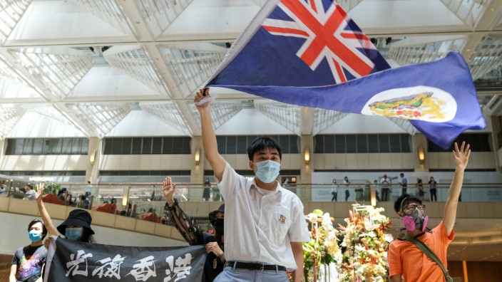 A pro-democracy demonstrator waves the British colonial Hong Kong flag during a protest against new national security legislation in Hong Kong