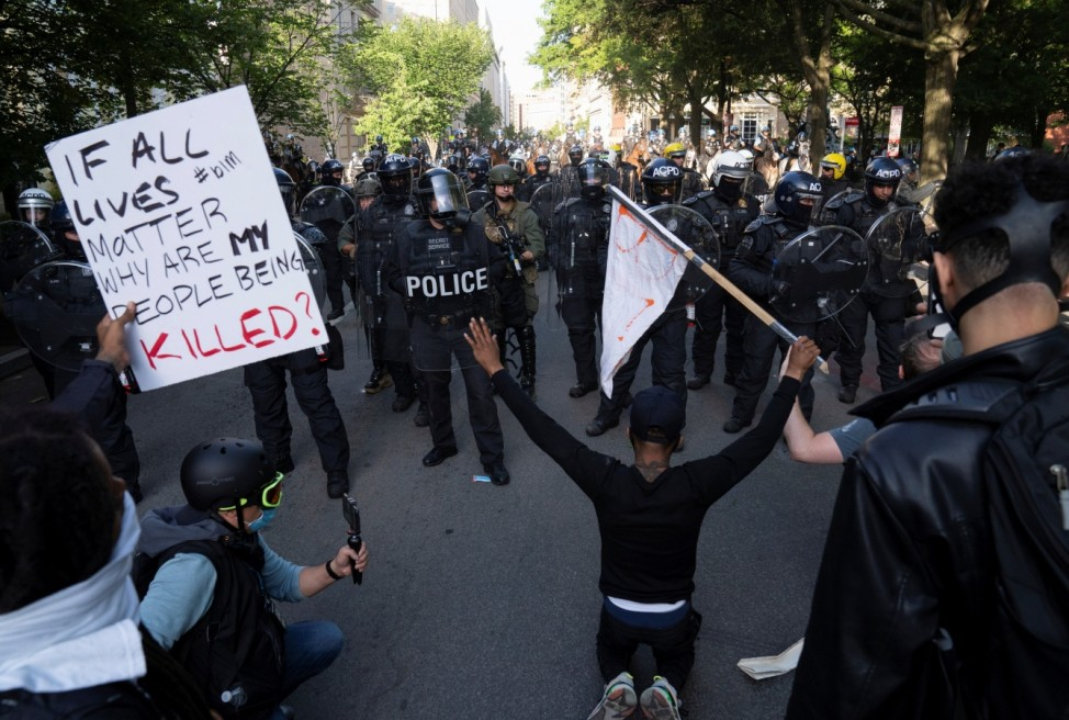 Protestors kneel as riot police clear Lafayette Park for a photo opportunity by President Donald Trump in Washington