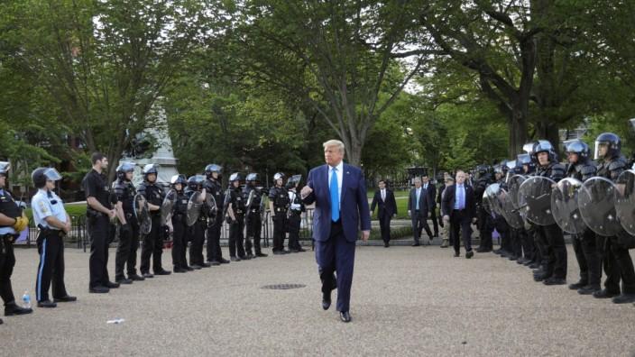 U.S. President Trump walks between lines of riot police in Washington