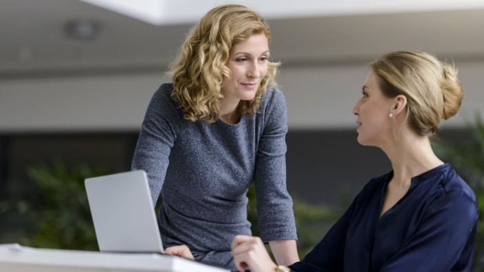 Two women talking at desk in office model released Symbolfoto property released PUBLICATIONxINxGERxSUIxAUTxHUNxONLY BMOF