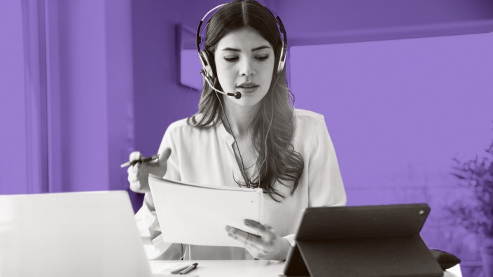 Young woman sitting at table at home wearing a headset model released Symbolfoto property released P