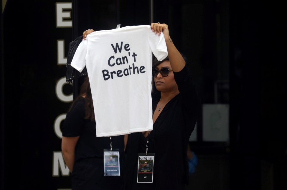 A woman holds a t-shirt that reads 'We Can't Breathe' outside the memorial service for George Floyd following his death in Minneapolis police custody, in Minneapolis