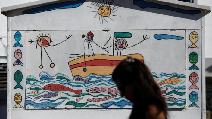 A person walks past a graffiti on a kiosk at the Praia da Luz beach