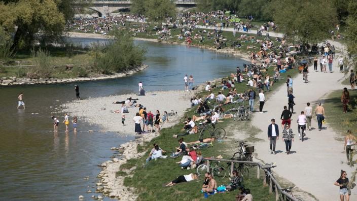 Schmuckfotos München. Menschenmassen draussen an der Isar trotz Ausgangsbeschränkung. Fotografiert von der Wittelsbacher Brücke.