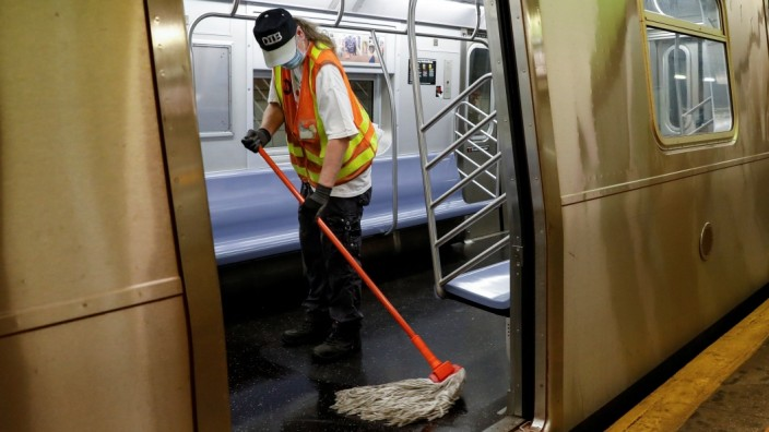 An MTA worker cleans a subway car during the morning commute, as phase one of reopening after lockdown begins, during the outbreak of the coronavirus disease (COVID-19) in New York