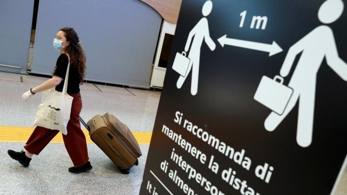 Frau mit Koffer und Mundschutz im Flughafen von Rom