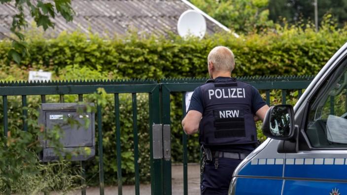 Kindermissbrauch in Münster Gesellschaft: Verbrechen, Prozesse. Ein Polizist steht am Eingang der Kleingartenanlage in M