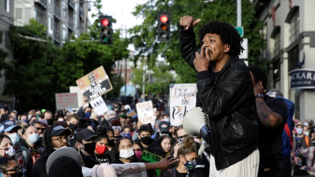 Protesters demonstrate outside the Seattle Police Department's East Precinct after the building was boarded up and vacated