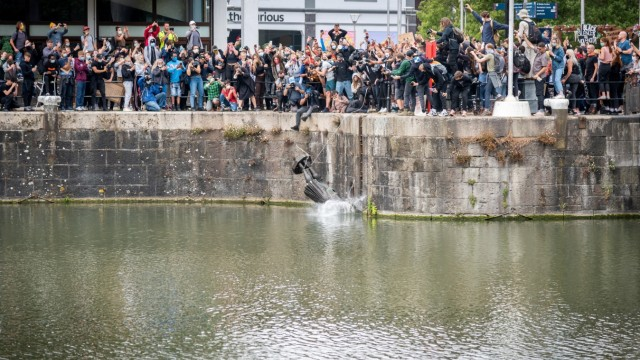 The statue of Edward Colston falls into the water after protesters pulled it down and pushed into the docks, following the death of George Floyd who died in police custody in Minneapolis, in Bristol