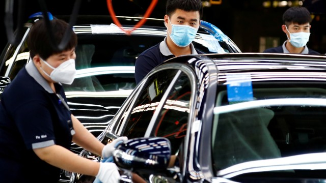 FILE PHOTO: Employees wearing face masks work at a plant of Daimler-BAIC joint ventureâÄÖs Beijing Benz Automotive Co during a government organised tour of the facility following the outbreak of the coronavirus disease (COVID-19), in Beijing