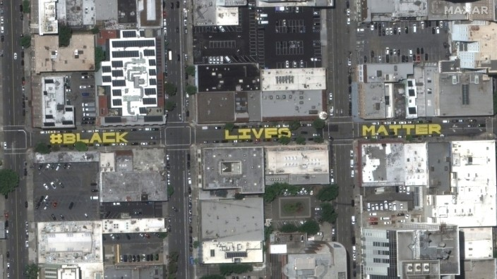 Giant letters spelling out the slogan 'Black Lives Matter' are painted on the road along 15th Street in downtown Oakland, California