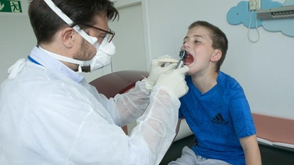 Kinderarzt-Versorgung im Münchner Norden. Behandlungssituation mit Kinderarzt Philip Wintermeyer und seinem Sohn Benedikt (gestellt). Racheninspektion