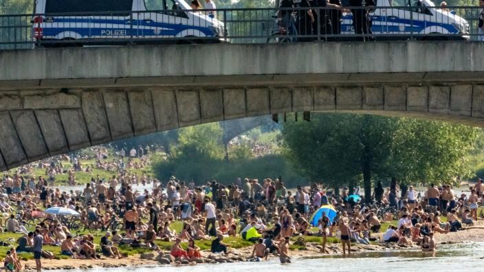 Menschen während Corona an der Isar, die Polizei auf der Reichenbachbrücke schaut zu