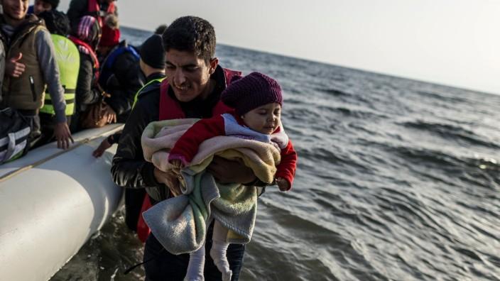 Flüchtlinge auf Lesbos - Fotostory Ein Flüchtig trägt am 29.02.2016 in der Naehe von Mytilini, Griechenland sein Kind a