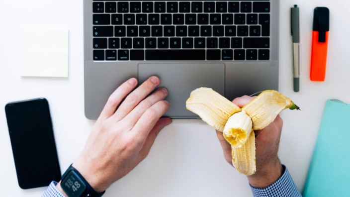 Mittagspause am Computer - Hands of man typing on laptop and eating banana model released Symbolfoto JCMF00630