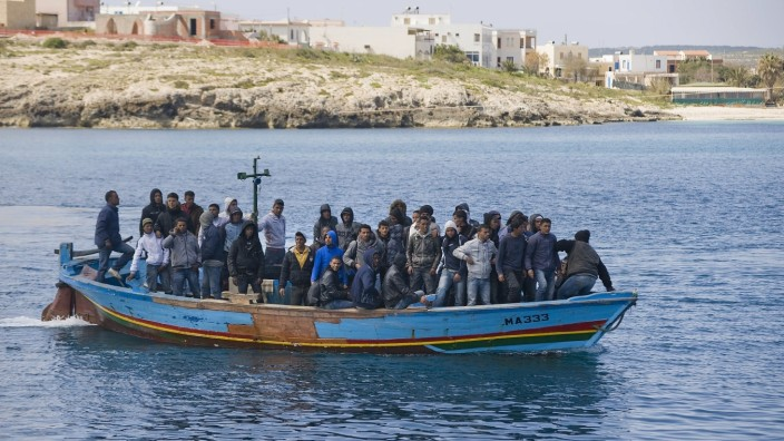 Arrival of a boat carrying refugees from north Africa. Lampedusa, immigrants at the port. Italian ship to transfer hund