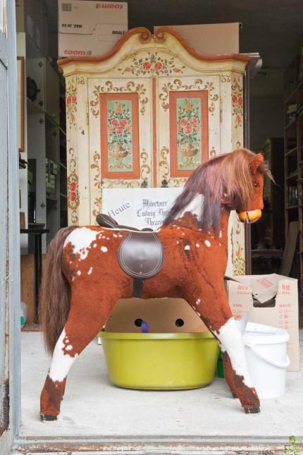 Kultur: Vor einem alten, kunstvoll bemalten Bauernschrank steht ein kleines Stoffpferd mit wallender Mähne.