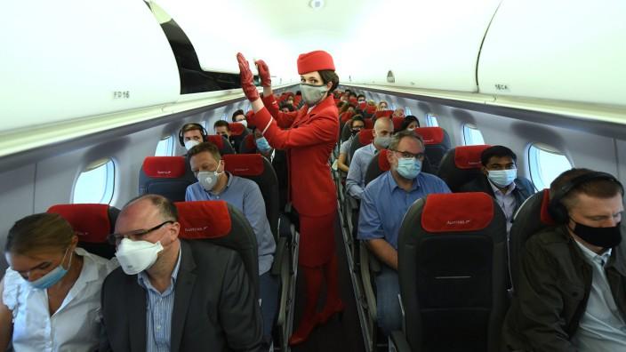 Passagiere mit Mundschutz sitzen in einem Flugzeug.