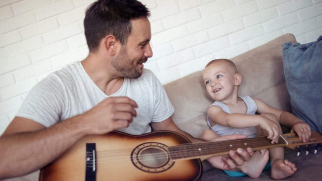 Father teaching his son how to play guitar.; Kinder Musik