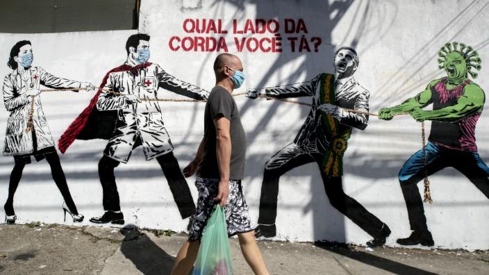 Brasilien: Ein Graffito in Sao Paulo zeigt ein Tauziehen zwischen Ärzten auf der einen Seite und Brasiliens Präsident Bolsonaro auf der anderen. Unterstützt wird der Staatschef dabei vom Coronavirus.
