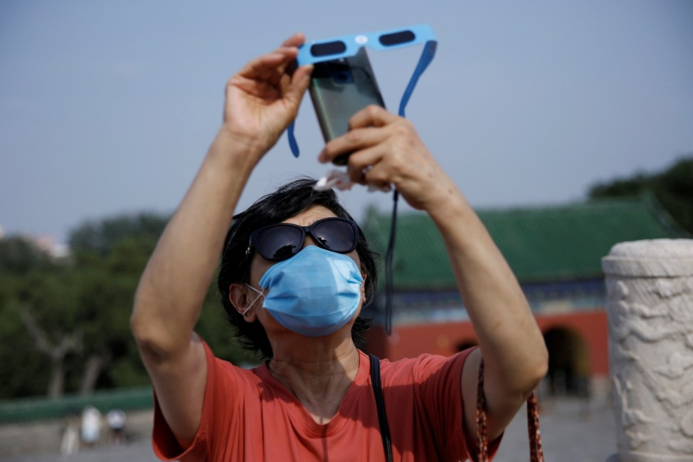 Woman wearing a face mask holds protective glasses in fron tof her phone as she captures the partial solar eclipse at the Temple of Heaven park, following an outbreak of the coronavirus disease (COVID-19), in Beijing