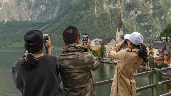 Asiatische Touristen fotografieren die Altstadt von Hallstatt.