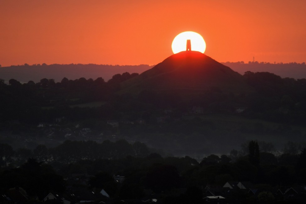 The sun is seen rising behind the remains of Saint Michael's Church on top of Glastonbury Tor, in Glastonbury