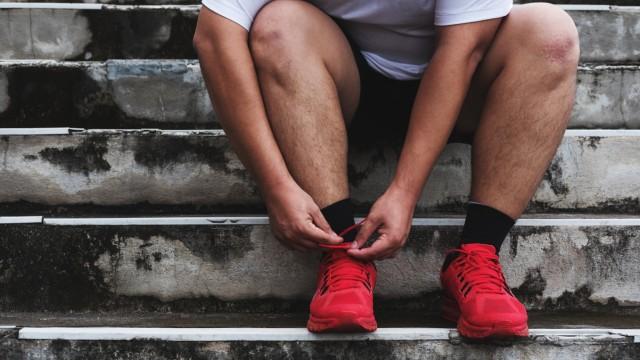 Asian Guy Tying Running Shoe, Preparing to Running for Losing Weight; Laufen