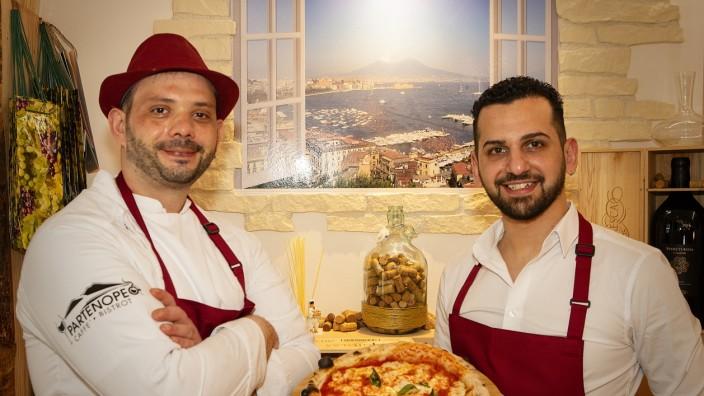 Lokalrunde: Koch Francesco Sardegna (links) und Inhaber Francesco Valletta präsentieren ihre Pizza vor einer neapolitanischen Fototapete.