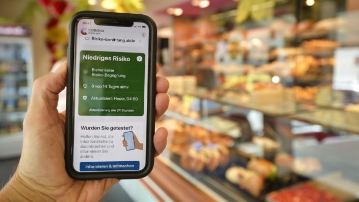 Hand hält Smartphone mit Corona Warn-APP in der Bäckerei, Corona-Krise, Stuttgart, Baden-Württemberg, Deutschland Coron