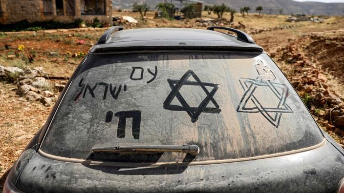 """Israelis und Palästinenser: Der Davidstern und die Worte """"Das Volk Israel lebt"""" auf Hebräisch sind auf dieser verstaubten Heckscheibe eines Autos nahe der Siedlung Itamar im Westjordanland zu sehen."""