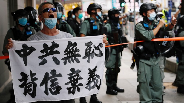 An anti-national security law protester holds a banner reading 'Chinese communist party is shameless, break the promises' during a march at the anniversary of Hong Kong's handover to China from Britain in Hong Kong
