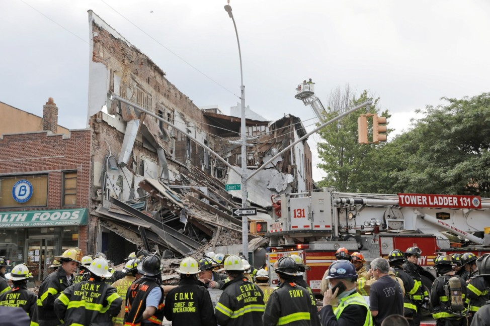 Members of the New York Fire Department (FDNY) inspect a collapsed building in the Brooklyn borough of New York City