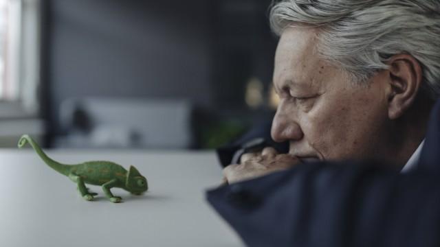 Senior businessman looking at toy chameleon model released Symbolfoto property released PUBLICATIONxINxGERxSUIxAUTxHUNxO