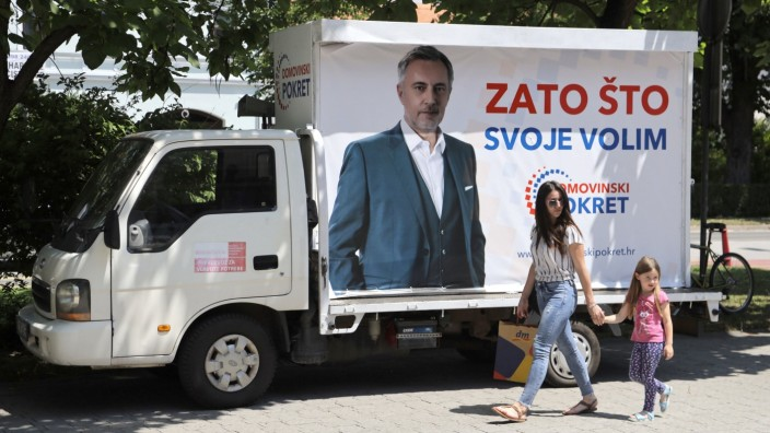 A woman with a child walks next to a truck with an election poster picturing Miroslav Skoro, leader of the Homeland Movement party, in Velika Gorica