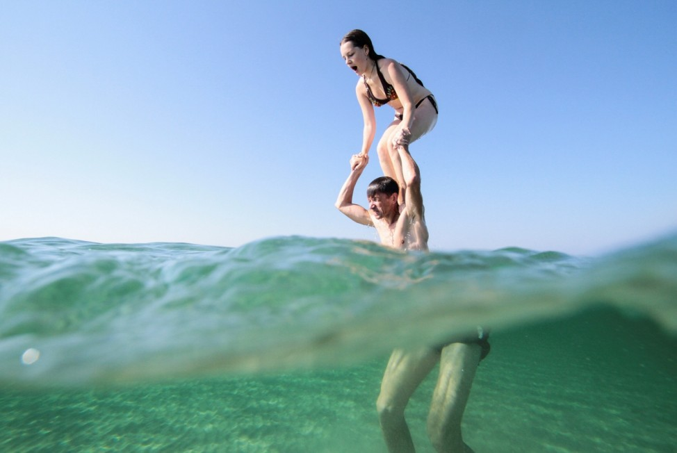 A man and his daughter swim in the waters of the Black Sea in Crimea