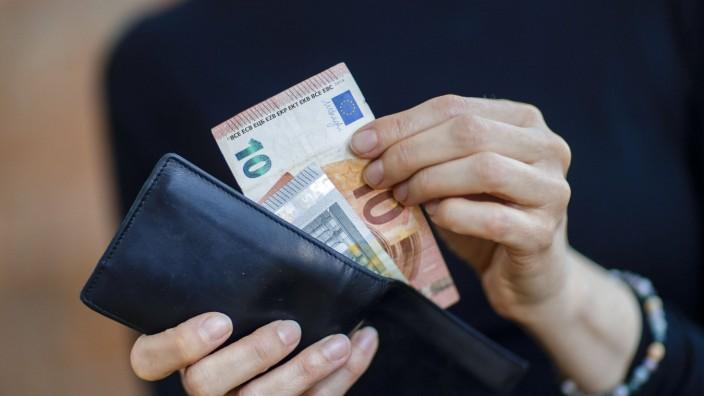 Symbolfoto. Eine Frau nimmt Geldscheine aus einer Geldboerse. Berlin, 06.04.2020.